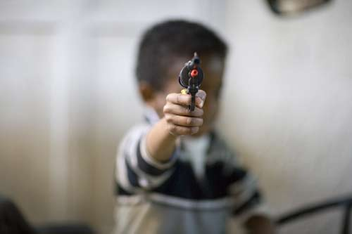 Jeruslem kid pointing toy gun at camera