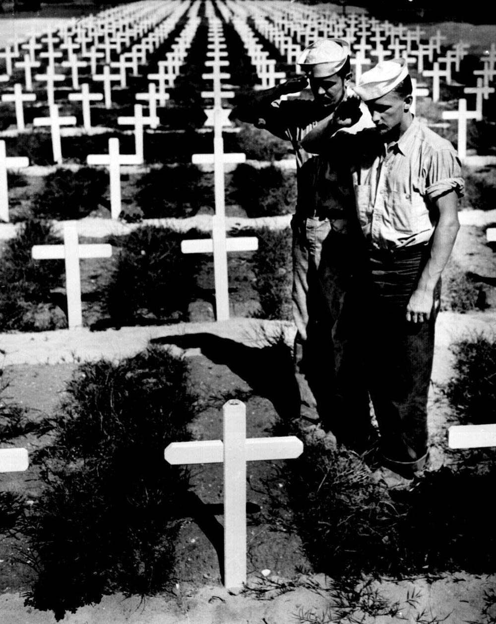 World War Two U.S. Coast Guardsmen saluting the grave of a fellow Guardsmen who died in action in the Ryukyu Islands. Benrud