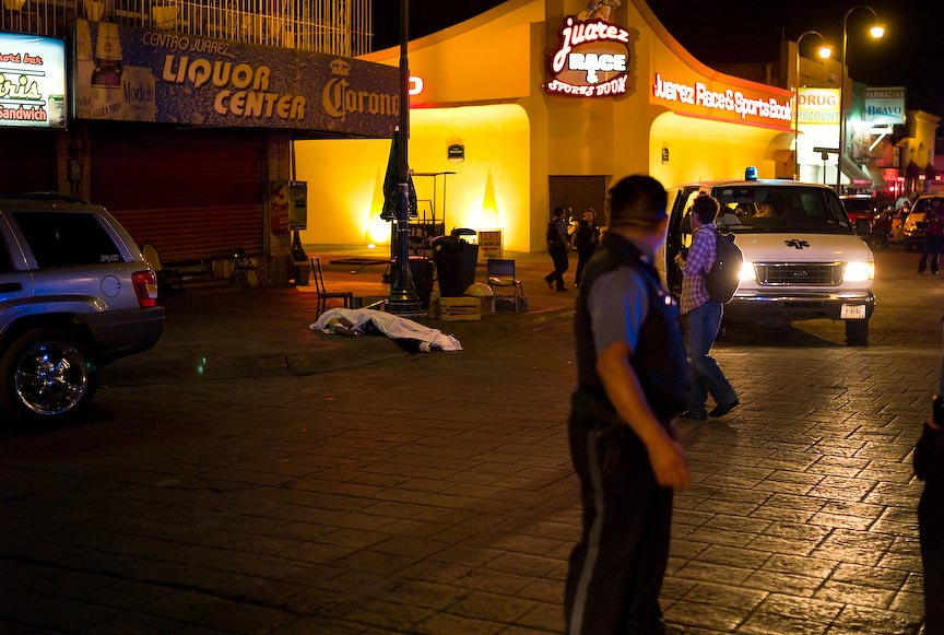 Juárez: dead body with police and onlookers, nighttime; © Julián Cardona