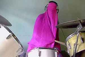 Girl at drums covered in pink burqa