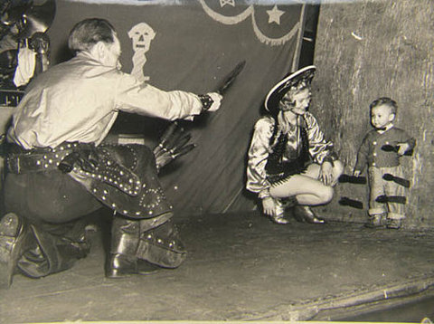 Man in circus throwing knives at boy