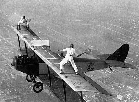 Two men playing tennis on wings of airplane in flight
