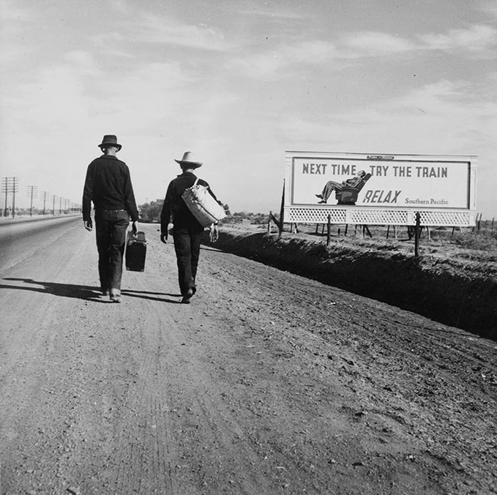 Two men walking, maybe hitchhiking, along a road past a billboard that says: Next time, try the train. Relax. 1937