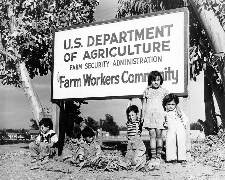 Children under sign that reads: U.S. Department of Agriculture Farm Security Administration Farm Workers Community
