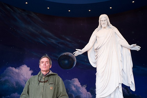 Scott Carrier below a religious statue, photo by Julian Cardona
