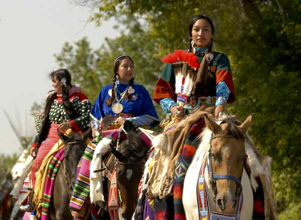 Crow women in dance dresses on horseback
