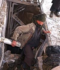Worker bringing coats up from the Qala-i-Jhangi basement