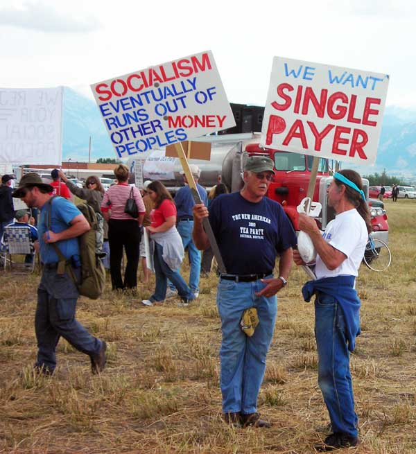 Two men talking, one with anti-socialism sign, the other with single-payer sign
