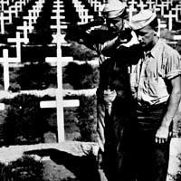 Soldiers salute at grave