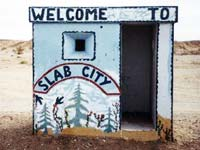 Hut painted with words: Welcome to Slab City