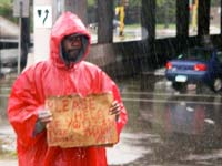 Man with sign in rain on interstate entrance