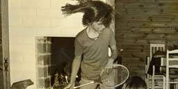 Nina playing air guitar on badmitten racket as a kid