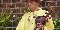 Manop Thammadoonpinij, music teacher and luthier, specializing in traditional Lanna music, playing the Pin Pia, at the street market in Chiang Mai, Thailand.