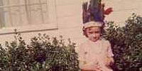 Sarah as a child wearing Indian chief headdress