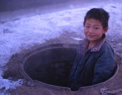 Street kid pops head out of manhole entrance to sewers