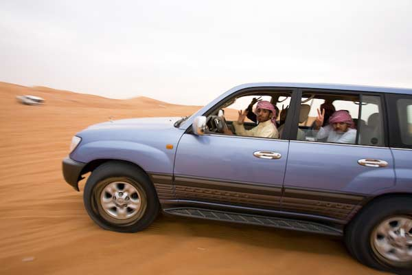Dune bashing in Dubai, Arabs in SUV riding in desert